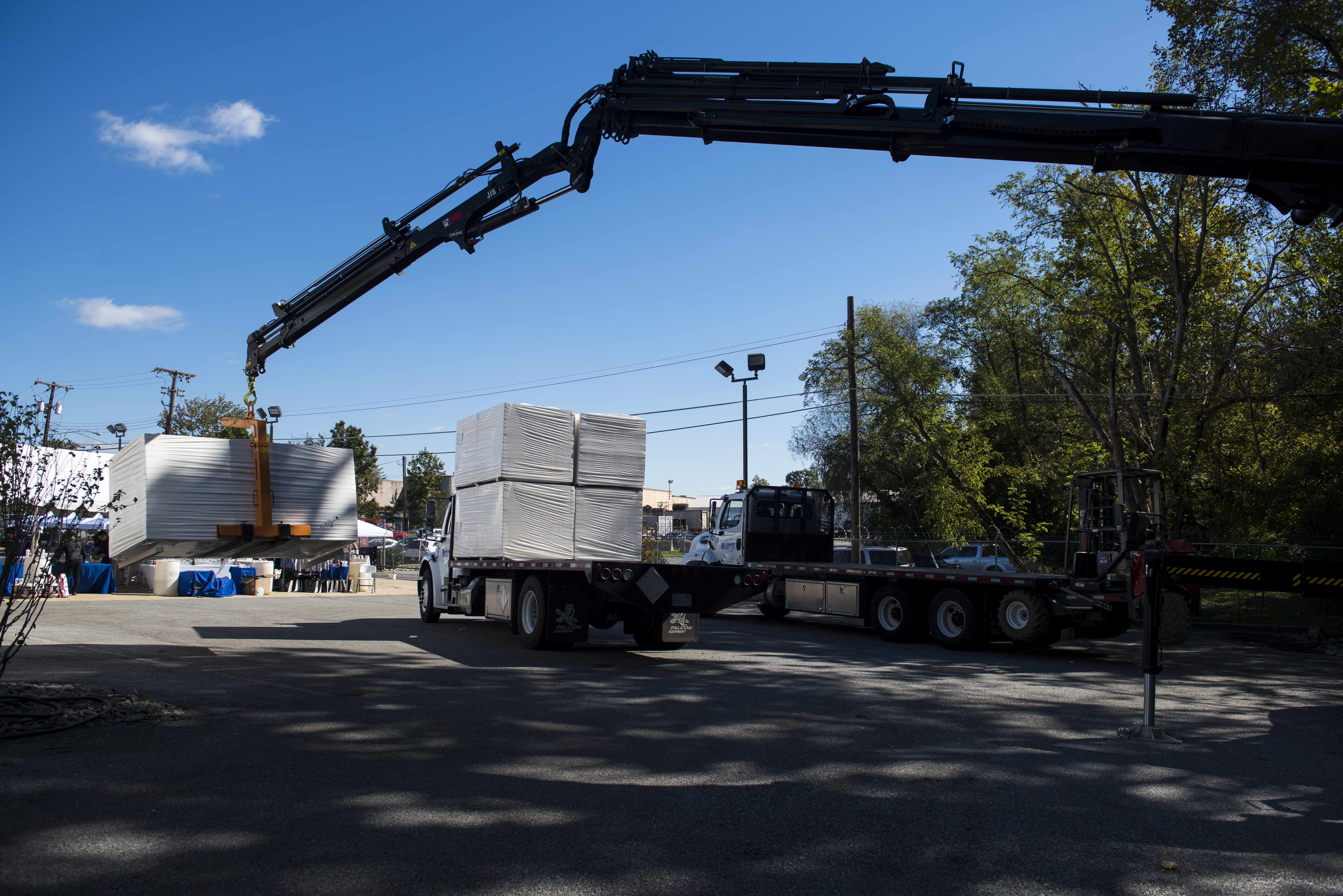 A crane loading a truck with insulation